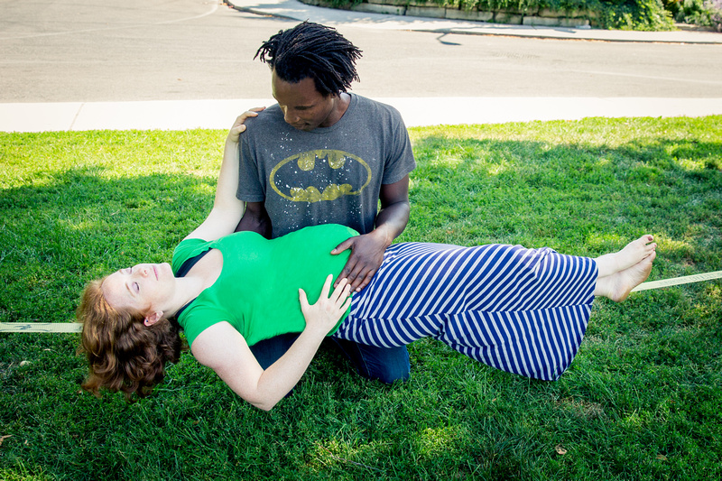 Pregnant woman lying on slackline with assistance.