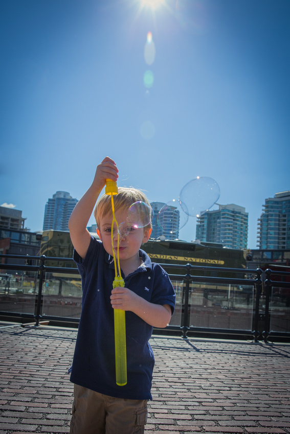 Boy blowing bubbles against the backdrop of the Toronto skyline