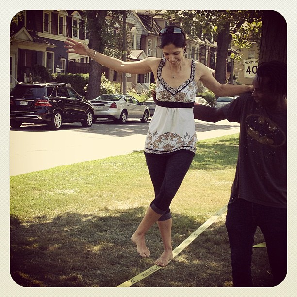 Woman walking on slackline with assistance