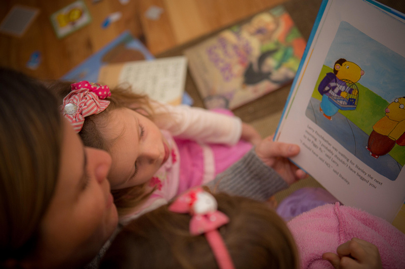 Girl reading book with mother