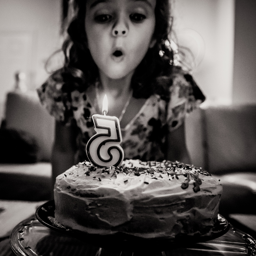 Girl blowing out candle on top of carrot cake with cream cheese icing for her fifth birthday